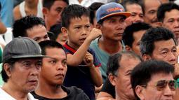 Seorang bocah Filipina menirukan gerakan Manny Pacquiao sambil menonton siaran langsung pertandingan bersama para orang tua di Manila (13/4/2014). (REUTERS/Romeo Ranoco)