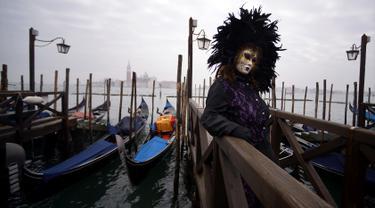 Peserta mengenakan kostum dan topeng berpose untuk difoto saat berpartisipasi dalam Karnaval Venesia di Italia (27/1). Karnaval Venesia adalah festival yang rutin diadakan setiap tahunnya di kota Venesia, Italia. (AFP Photo/Filippo Monteforte)