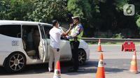 Petugas kepolisian berbincang dengan pengendara di pos penyekatan pemudik Tol Cikarang Barat, Kabupaten Bekasi, Jawa Barat, Minggu (9/5/2021).Petugas gabungan memperketat pemeriksaan dokumen kendaraan yang melintasi pos penyekatan pemudik jelang H-3  Idul Fitri 1442 H. (Liputan6.com/Herman Zakharia)