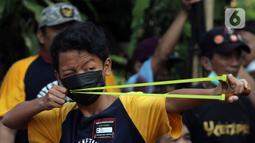Peserta membidik sasaran saat lomba ketapel di Kampoeng Ketapel, Ciganjur, Jakarta, Minggu (19/9/2021). Ketapel diharapkan bisa menjadi salah satu olahraga prestasi yang diakui KONI. (Liputan6.com/Herman Zakharia)