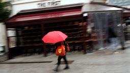 Seorang perempuan berjalan melewati tumpukan kursi dan meja dari bar The First yang tutup di Brussel, Belgia, Kamis (8/10/2020). Brussels pada Rabu (7/10), memutuskan menutup semua bar, ruang dansa, dan kafetaria selama sebulan sebagai upaya membendung lonjakan COVID-19. (AP Photo/Francisco Seco)