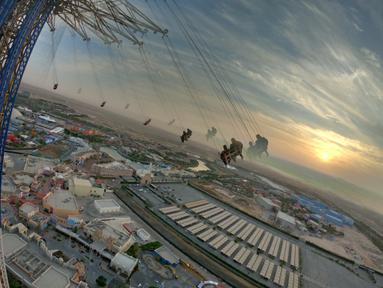 Orang-orang menaiki sky flyer di Taman Bollywood di Dubai (18/2/2021). Menjulang hingga 140 meter, Sky Flyer di Taman Bollywood, Dubai, memecahkan rekor dunia sebagai ayunan tertinggi dunia. (AFP/ Giuseppe Cacae)