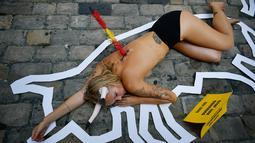 Aktivis yang bertelanjang dada berbaring di jalan saat menggelar protes terhadap adu banteng di Pamplona, Spanyol, Jumat (5/7/2019). Para aktivis menempelkan tombak palsu pada punggung mereka sebagai simbol penyiksaan hewan dalam adu banteng di Festival San Fermin. (AP Photo/Alvaro Barrientos)
