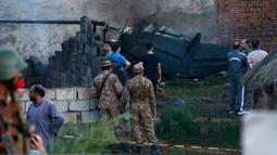 Pejabat militer Pakistan memeriksa lokasi kecelakaan pesawat di Rawalpindi, Pakistan, Selasa (30/7/2019). Korban tewas termasuk dua pilot dan tiga kru pesawat. (AP Photo/Anjum Naveed)