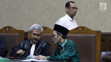 Terdakwa dugaan suap seleksi pengisian jabatan di Kementerian Agama, Haris Hasanuddin (berdiri) dan M Muafad Wirahadi (kanan duduk) saat jeda sidang lanjutan di Pengadilan Tipikor, Jakarta, Rabu (10/7/2019). Sidang mendengar keterangan saksi. (Liputan6.com/Helmi Fithriansyah)
