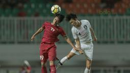 Duel pemain Timnas Indonesia U-23, Hanif Syahbandi (kiri) dengan pemain Korea Selatan U-23, Lee Seung-mo pada laga uji coba di Stadion Pakansari, Bogor, (23/6/2018).  Indonesia U-23 kalah 1-2 dari Korea U-23. (Bola.com/Nick Hanoatubun)