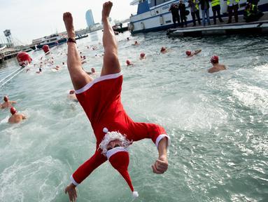 Seorang peserta dalam kostum sinterklas melompat ke air saat  kompetisi renang Copa Nadal di Port Vell Barcelona, Selasa (25/12). Lomba tradisional ini sudah menjadi tradisi lama yang mereka lakukan tiap tahun pada hari natal. (Josep LAGO / AFP)