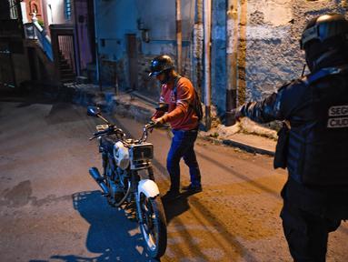 Anggota polisi bersiap menggeledah warga dalam operasi di tengah pandemi COVID-19 di Los Teques, negara bagian Miranda, Venezuela, 20 Maret 2021. Di Miranda ada pembatasan keluar sejak pukul 18.00 dan perintah penutupan toko pada pukul 16.00 di tengah gelombang kedua pandemi. (Federico PARRA/AFP)