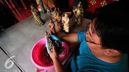 Warga keturunan Tionghoa mencuci sejumlah patung dewa di Klenteng Poncowinatan, Yogyakarta, Selasa (2/2/2016). Patung patung dewa di bersihkan untuk menyambut perayaan imlek. (Liputan6.com/Boy Harjanto)