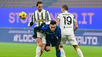 Striker Inter Milan, Lautaro Martinez (tengah) dihadang dua pemain Juventus, Adrien Rabiot (kiri) dan Leonardo Bonucci dalam laga lanjutan Liga Italia Serie A 2020/21 pekan ke-18 di San Siro Stadium, Minggu (17/1/2021). Inter Milan menang 2-0 atas Juventus. (AFP/Miguel Medina)