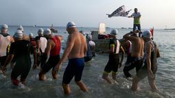 Peserta menuju bibir pantai sebelum berenang ketika Rhino Cross Triathlon 2018 di Kawasan Tanjung Lesung, Pandeglang, Banten, Minggu (30/9). Rhino Cross Triathlon digelar untuk meningkatkan potensi wisata Tanjung Lesung. (Liputan6.com/HO/Nick Hanoatubun)
