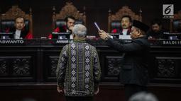 Marsudi Wahyu Kisworo, ahli yang dibawa oleh tim hukum KPU disumpah sebelum memberikan keterangan dalam sidang lanjutan sengketa Pilpres 2019 di Gedung MK, Jakarta, Kamis (20/6/2019). Sidang mendengarkan keterangan saksi dan ahli dari pihak termohon, yaitu KPU RI. (Liputan6.com/Faizal Fanani)