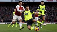 Gelandang Arsenal Lucas Torreira (kiri) berjibaku dengan penggawa Huddersfield Town Chris Lowe pada laga Liga Inggris di Emirates Stadium, Sabtu (8/12/2018). (Isabel Infantes/PA via AP)