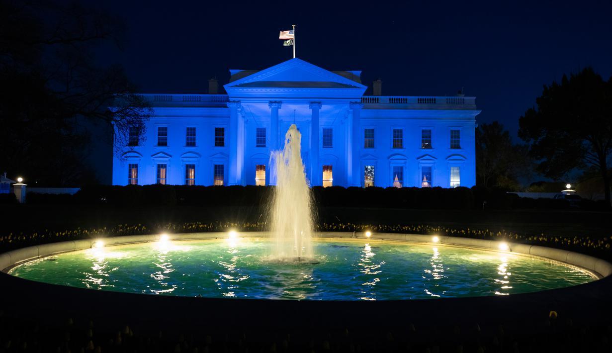 Gedung Putih diterangi dengan cahaya warna biru untuk menarik perhatian pada World Autism Awareness Day atau Hari Peduli Autisme Sedunia di Washington, Kamis (2/4/2020). Hari Peduli Autisme Sedunia jatuh setiap 2 April semenjak ditetapkan melalui sebuah resolusi PBB di tahun 2007. (AP/Alex Brandon)