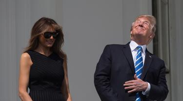 Presiden AS Donald Trump bersama Ibu Negara, Melania Trump menyaksikan  gerhana matahari dari balkon Gedung Putih di Washington, Senin (21/8). Trump tertangkap kamera menyaksikan fenonema langka tersebut tanpa kacamata pelindung. (NICHOLAS KAMM/AFP)