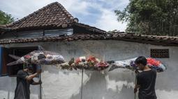Aktivis Ecological Observation and Wetland Conservation (Ecoton) menjemur sampah plastik untuk membuat instalasi di Gresik, Jawa Timur, 17 September 2021. Instalasi tersebut untuk meningkatkan kesadaran masyarakat akan sampah plastik di sungai dan lautan. (JUNI KRISWANTO/AFP)