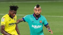 Pemain Villareal, Andre-Frank Zambo Anguissa berebut bola dengan gelandang Barcelona, Arturo Vidal dalam pekan ke-34 La Liga Spanyol di stadion La Ceramica, Minggu (5/7/2020). Barcelona sukses menumbangkan tim tuan rumah Villarreal dengan skor telak 4-1. (AP Photo/Jose Miguel Fernandez)