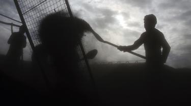 Buruh Afghanistan bekerja di pasar arang di pinggiran Kabul, Afghanistan (18/12/2019). Di musim dingin, harga kayu dan arang naik di antara semua kebutuhan lain untuk warga Afghanistan. (AP Photo / Rahmat Gul)