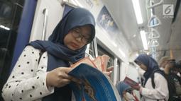 Masyarakat pengguna MRT tengah membaca buku yang disediakan disetiap stasiun MRT di Jakarta, Minggu (8/9/2019). Pemprov DKI Jakarta  meluncurkan ruang baca buku disetiap stasiun MRT untuk menumbuhkan minat baca masyarakat. (Liputan6.com/Angga Yuniar)