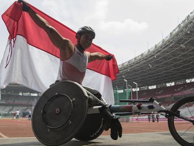 Pebalap kursi roda Indonesia, Jaenal Aripin, melakukan selebrasi usai meraih medali perak pada Asian Para Games cabang atletik nomor balap kursi roda 200 meter T 54 di SUGBK, Jakarta, Jumat (12/10). (Bola.com/Vitalis Yogi Trisna)