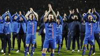 Kapten Islandia, Aron Gunnarsson, bersama rekan- rekan nya melakukan selebrasi usai memastikan negaranya lolos Piala Dunia 2018 di Stadion Laugardalsvöllur, Senin (9/10/2017). Islandia menang 2-0 atas Kosovo. (AP/Brynjar Gunnarsson)