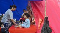 Seorang ibu memberi makan putrinya di tenda saat mereka berteduh sementara setelah gempa berkekuatan 6,2 skala Richter pada 15 Januari di Mamuju, Senin (18/1/2021). (AFP/Adek Berry)