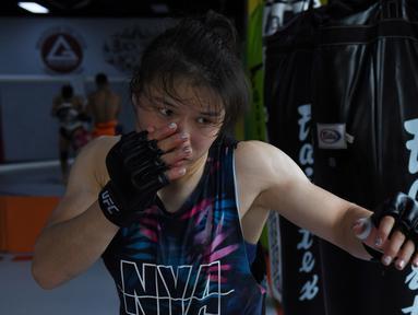 Petarung MMA China Zhang Weili memukul samsak selama sesi pelatihan di gym di Beijing (7/8/2019). Zhang bisa menjadi juara dunia UFC pertama asal China jika dapat mengalahkan pemegang gelar Jessica Andrade dari Brasil dalam pertarungan kelas berat mereka pada 31 Agustus 2019. (AFP Photo/Greg Baker)