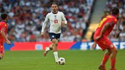 Jack Grealish menggunakan gaya berkaus kaki pendek sejak berseragam Aston Villa. Gelandang yang berstatus sebagai pemain termahal Manchester City tersebut mengungkapkan bahwa alasannya menggunakan gaya tersebut adalah sebagai keberuntungan. (AFP/Justin Tallis)