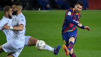Striker Barcelona, Lionel Messi (kanan) melepaskan tendangan yang berbuah gol keempat timnya ke gawang SD Huesca dalam laga lanjutan Liga Spanyol 2020/2021 pekan ke-27 di Camp Nou Stadium, Barcelona, Senin (15/3/2021). Barcelona menang 4-1 atas SD Huesca. (AFP/Lluis Gene)