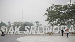 Sejumlah wanita berpose saat mengunjungi alun-alun Kabupaten Siak, Riau, Kamis (12/9/2019). Asap pekat kebakaran lahan gambut tersebut selain mengganggu kesehatan serta mencemari udara sehingga kualitasnya turun ke status tidak sehat. (Liputan6.com/Faizal Fanani)