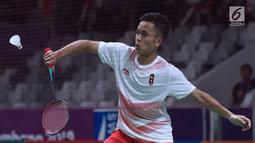 Tunggal putra Indonesia, Anthony Sinisuka Ginting mengembalikan kok ke arah pemain Jepang, Kento Momota pada semifinal Bulutangkis Beregu Putra Asian Games 2018 di Jakarta, Selasa (21/8). (Liputan6.com/Helmi Fithriansyah)