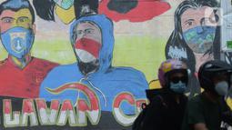 Pengendara motor melewati  mural anjuran kebiasan hidup baru dengan 3 M di Stasiun Cawang, Jakarta, Sabtu (26/12/2020). Pemerintah terus berupaya melakukan imbauan kepada warga untuk melaksanakan kebiasaan baru 3M guna memutus penyebaran virus corona (COVID-19). (merdeka.com/Imam Buhori)