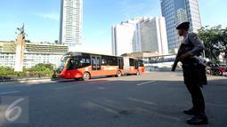 Bus Transjakarta melintas saat anggota kepolisian berjaga di kawasan Bundaran HI, Jakarta, Senin (1/5). Ratusan aparat kepolisian dikerahkan melakukan pengamanan demo buruh memperingati May day di sekitaran Bundaran HI. (Liputan6.com/Johan Tallo)