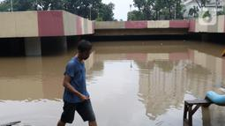 Warga melihat banjir yang mengenangi underpass Kemayoran, Jakarta, Minggu (2/2/2020). Banjir kembali merendam underpass Kemayoran, Jakarta Pusat. Akibatnya, akses jalur tersebut pun terputus alias tak bisa dilalui kendaraan. (Liputan6.com/Angga Yuniar)