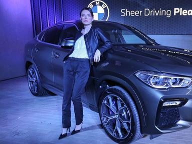 Model berpose di mobil all-new BMW X6 saat peluncuran di German Centre BSD, Tangerang Selatan. The News X6 yang memiliki desain tegas dan kokoh inovasi canggih seperti lampu Iconic Glow di BMW kidney grille diproduksi di Spartanburg,  South Carolina. (Liputan6.com/Fery Pradolo)