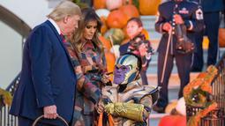 Halloween Ala Trump: Presiden Donald Trump dan ibu negara Melania Trump membagikan permen kepada anak-anak selama acara trick-or-treat Halloween di Gedung Putih, 28 Oktober 2019. Halloween memang menjadi salah satu perayaan terbesar di banyak negara di seluruh dunia. (AP/Alex Brandon)