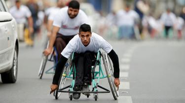 Sejumlah warga difable Palestina mengayuh roda saat bersaing dalam perlombaan kursi roda yang diselenggarakan oleh Masyarakat Amal Assalama di Kota Gaza, (29/11). (REUTERS/Suhaib Salem)
