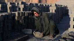 Foto pada 27 Maret 2018, perempuan Afghanistan, Sitara Wafadar menyamar sebagai laki-laki saat bekerja di pabrik batu bata di Provinsi Nangarhar. Sitara dipaksa orangtuanya menjadi seorang 'putra' yang tidak pernah mereka miliki. (NOORULLAH SHIRZADA/AFP)