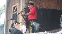 """Iwan Fals saat menyanyikan lagu """"Kesaksian"""" yang dipersembahkan untuk mendiang Yockie Suryoprayogo di Seri Konser Situs Budaya, di Leuwinanggung, Sabtu (3/3/2018). (Liputan6.com/Edu Krisnadefa)"""