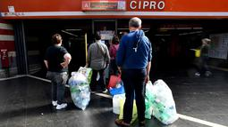 Penumpang antre menukarkan sampah botol plastik dengan tiket kereta menggunakan mesin daur ulang di stasiun metro bawah tanah Cipro, Roma, Selasa (8/10/2019). Warga harus memasang aplikasi di ponsel untuk mendapatkan barcode tiket elektronik setiap kali menukarkan botol plastik. (Tiziana FABI/AFP)