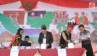 Petugas KPPS berpakaian tradisional melayani warga yang akan mencoblos di TPS 7 Panggung Lor, Semarang, Jawa Tengah, Rabu (17/4). Para petugas mengenakan pakaian khas Nusantara untuk menghibur dan menarik warga dalam memilih di Pemilu 2019. (Liputan6.com/Gholib)