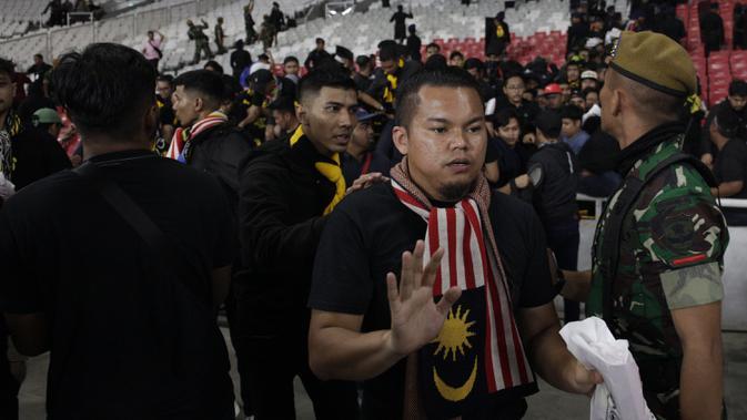 Suporter Malaysia dievakuasi karena serangan dari suporter Timnas Indonesia saat laga Kualifikasi Piala Dunia 2022 di SUGBK, Jakarta, Kamis (5/9). (Bola.com/Vitalis Yogi Trisna)