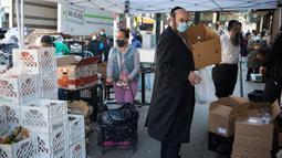 Orang-orang memilih bahan makanan di sebuah tempat distribusi makanan di Wilayah Brooklyn, New York, Amerika Serikat (AS), (14/5/2020). Jumlah klaim pengangguran awal di AS mencapai 2.981.000 pekan lalu. (Xinhua/Michael Nagle)