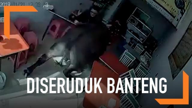 Seorang wanita berbaju merah dikejar dan diseruduk banteng hingga masuk ke sebuah tempat makan di China.