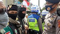 Polisi membubarkan paksa massa Aksi 1812 yang terkonsentrasi di kawasan Patung Kuda, Jalan Medan Merdeka Barat, Jakarta Pusat. (Liputan6.com/Yopi Makdori)