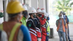 Pekerja mengenakan masker saat mengerjakan proyek pembangunan integrated building Bandara Internasional Soekarno-Hatta, Tangerang, Banten, Rabu (29/7/2020). Pembangunan gedung penghubung stasiun Bandara Soetta dan jembatan itu sudah mencapai 44,4 persen. (merdeka.com/Dwi Narwoko)