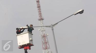 Pekerja memasang lampu light emitting diode (LED) di Jakarta, Selasa (26/7). Secara bertahap, Pemprov DKI akan menggunakan lampu LED yang lebih hemat energi untuk Penerangan Jalan Umum (PJU) di seluruh Jakarta. (Liputan6.com/Immanuel Antonius)