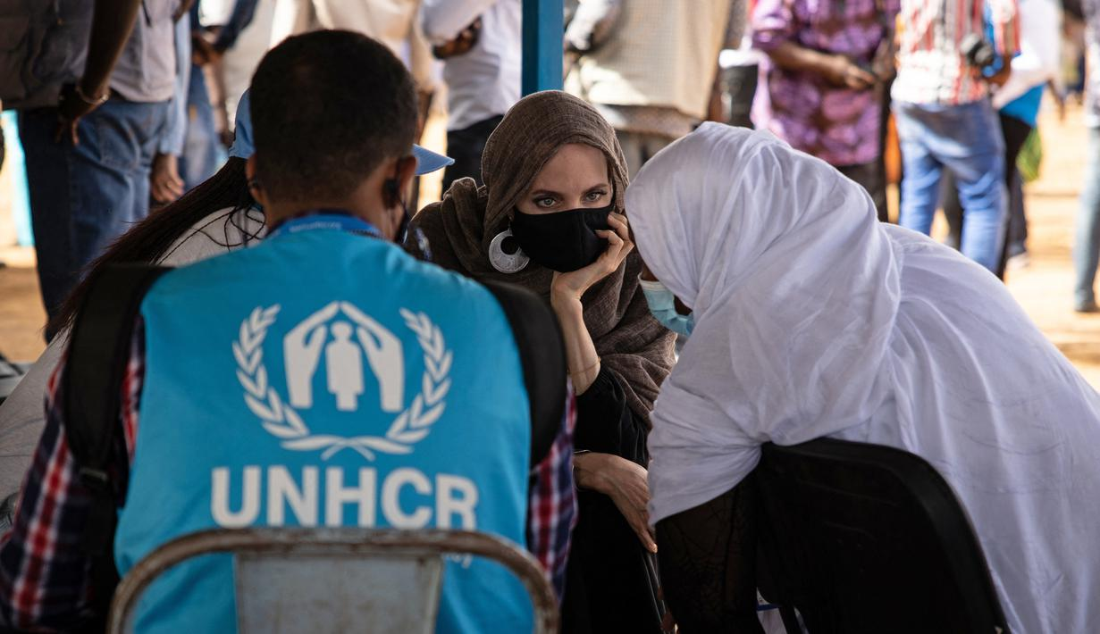 Aktris Angelina Jolie, utusan khusus PBB untuk UNHCR, berbincang dengan pengungsi Mali di kamp Goudebou, utara Burkina Faso, 20 Juni 2021. Jolie mengunjungi kamp pengungsi yang menampung ribuan warga Mali yang menyelamatkan diri dari kekerasan militan di kawasan itu. (OLYMPIA DE MAISMONT/AFP)