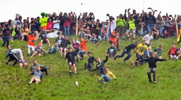 Peserta berlomba mengejar keju dalam kompetisi Cheese Rolling di Bukit Cooper, Gloucestershire, Inggris, Senin (27/5/2019). (Ben Birchall/PA via AP)