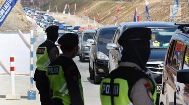 Petugas kepolisian mengatur kendaraan yang melintasi Tanjakan Kali Kenteng di jalan tol fungsional Salatiga-Boyolali, Jawa Tengah, Senin (18/6). Jalan tol ini akan dibukan selama 24 jam selama arus balik Lebaran 2018. (Liputan6.com/Gholib)